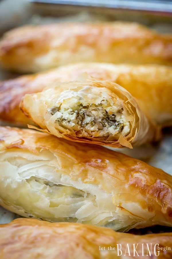 Greek pastries hand pies filled with creamy spinach and feta filling laid out in a row!