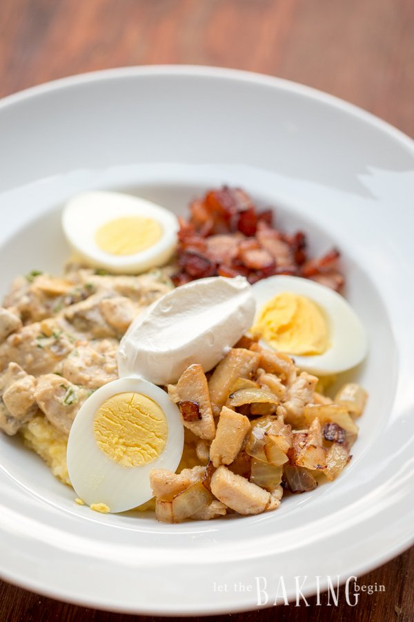 Polenta with egg, mushrooms, chicken, bacon, and sour cream in a white decorative bowl.