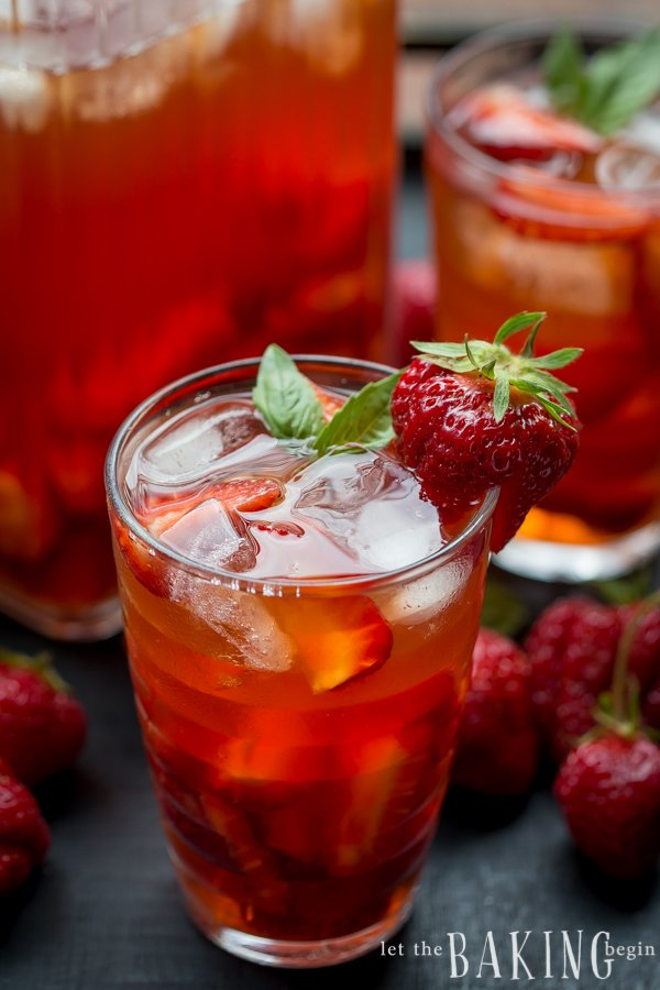 Strawberry iced tea in a glass cup topped with mint and strawberries.