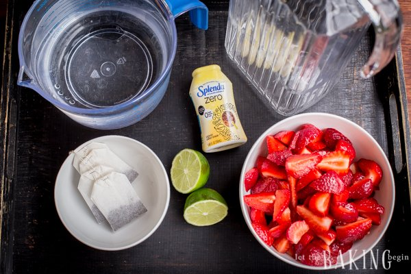 Boiling water, cold water, tea bags, sliced strawberries, sliced strawberries, splenda, and limes set out.