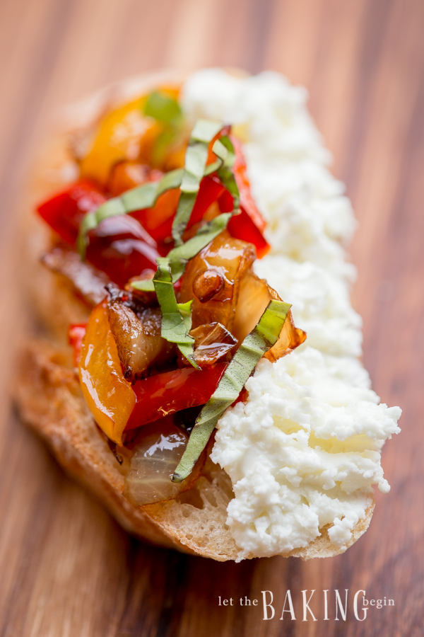 Close up picture of goat cheese, caramelized onions, and peppers topped with greens on a baguette.