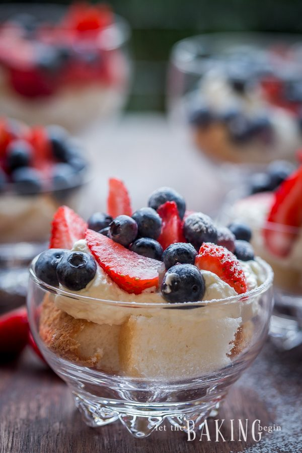 Cheesecake and berry trifle topped with blueberries and strawberries in a glass cup.