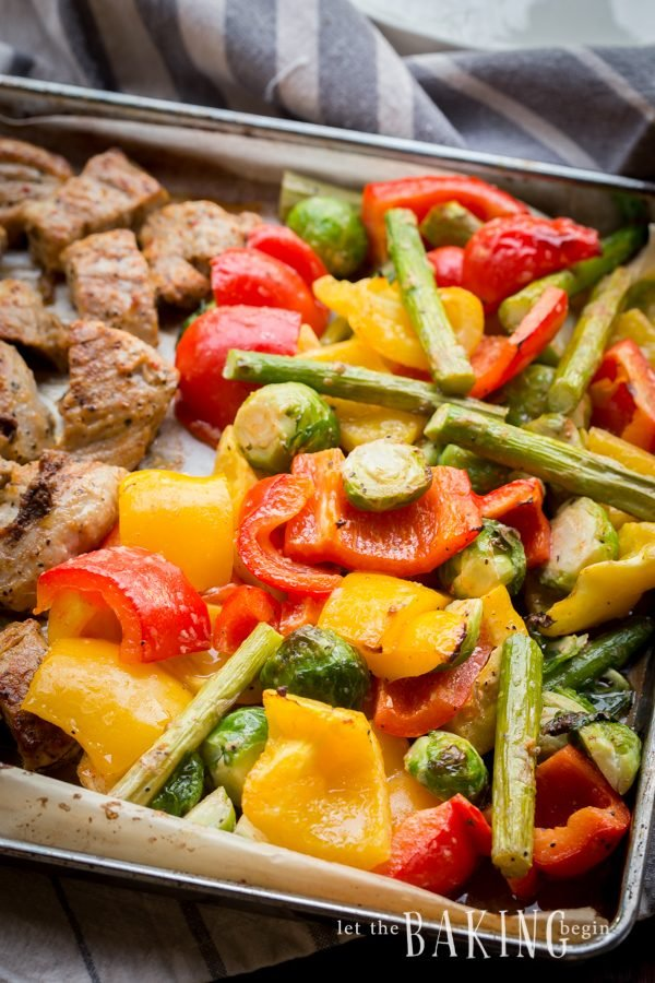 Roasted vegetables, peppers, brussel sprouts, and asparagus on a parchment lined baking sheet.