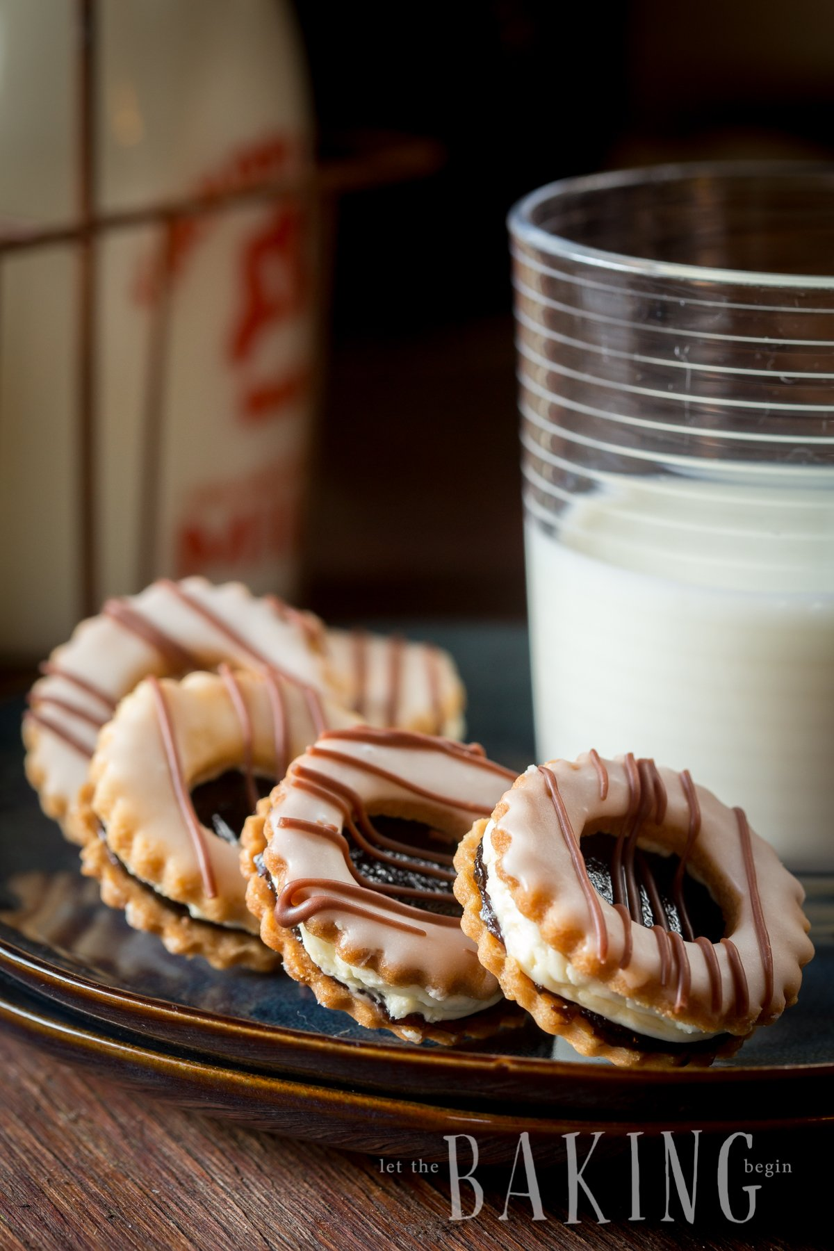 Pastry cookies filled with plum butter and buttercream on a plate with a glass of milk.