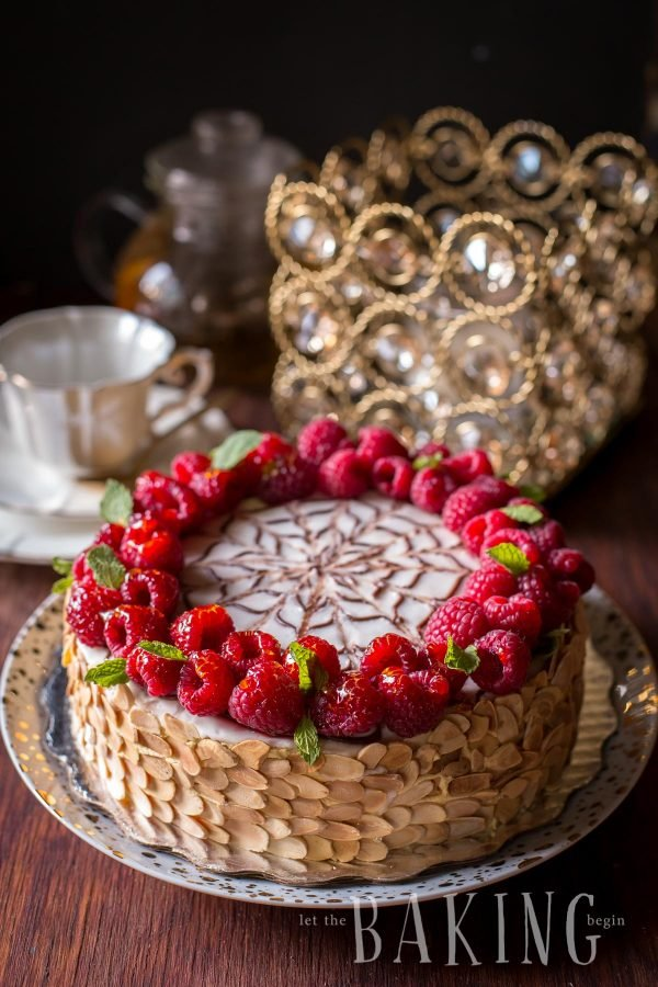 Esterhazy cake with almond slices and topped with fresh raspberries and mint on a cake platter.