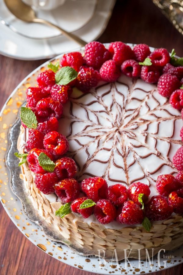 Hazelnut meringue cake with a custard buttercream topped with chocolate décor and raspberries.