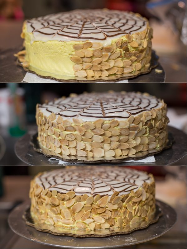 Lining the sides of the meringue cake with sliced almonds.