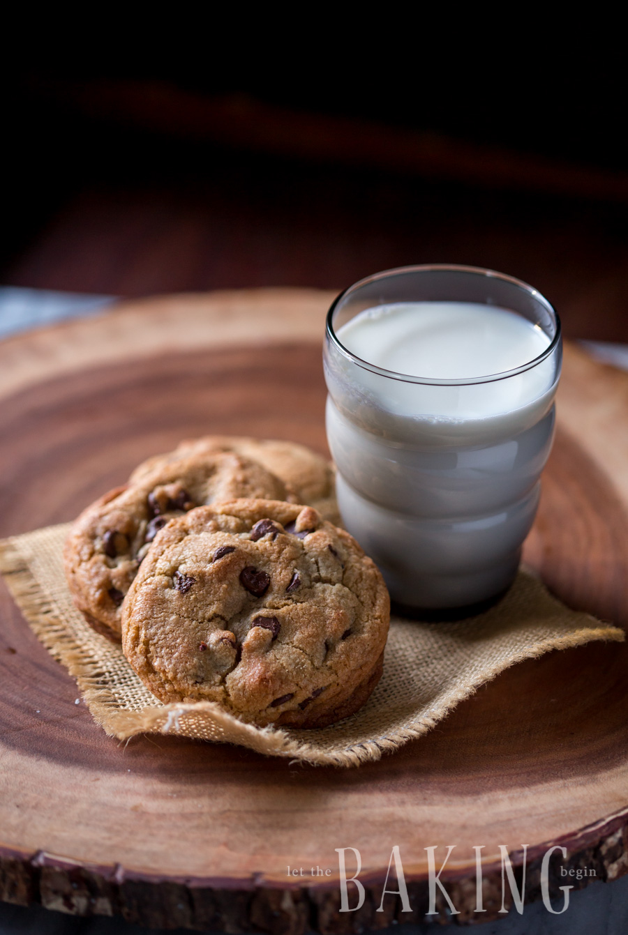 Three chewy chocolate chip cookies on burlap with a glass of milk.