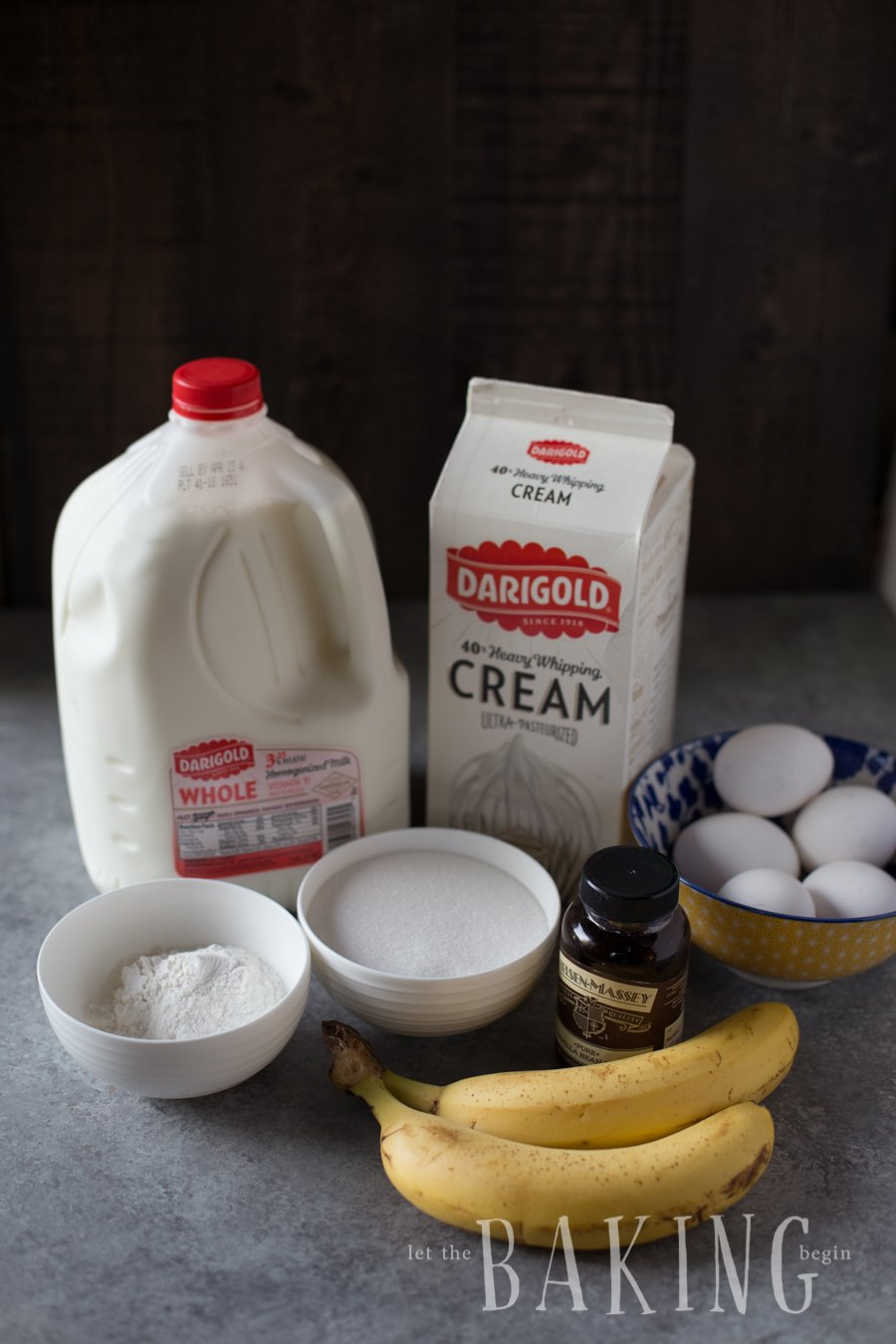 Graham crackers, egg yolks, eggs, sugar, flour, milk, heavy cream, and vanilla extract displayed on a counter top.