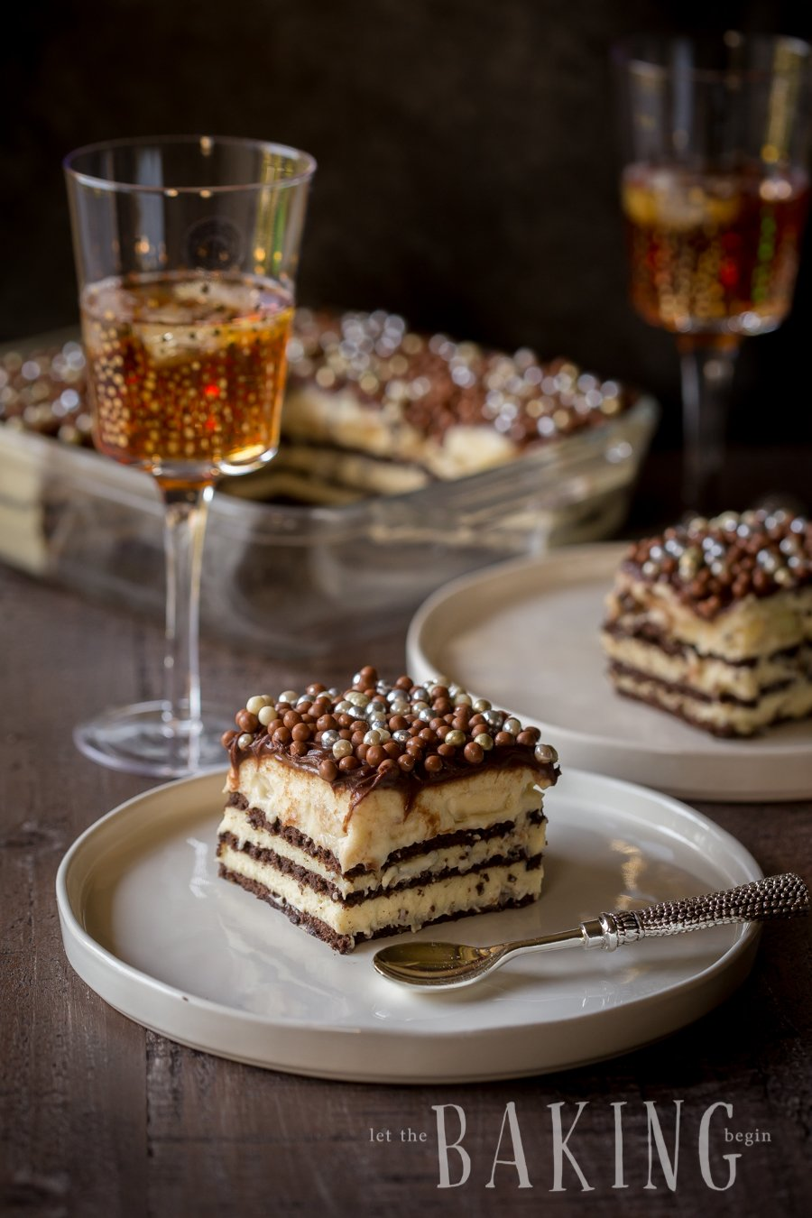 Piece of cake on a white plate topped with pearls on a wooden table.