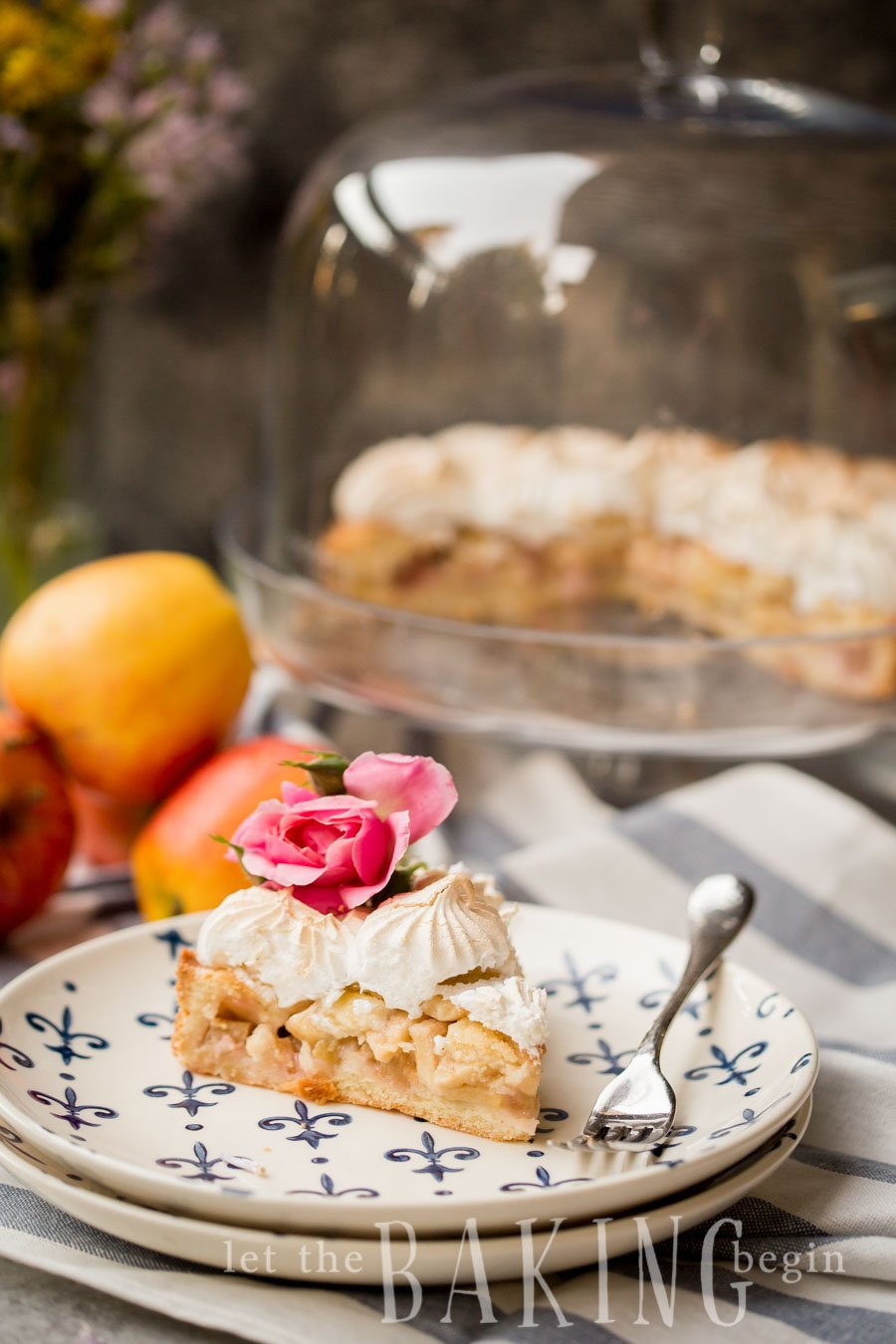 A slice of apple rhubarb meringue pirog on a plate topped with a pink flower with a fork.