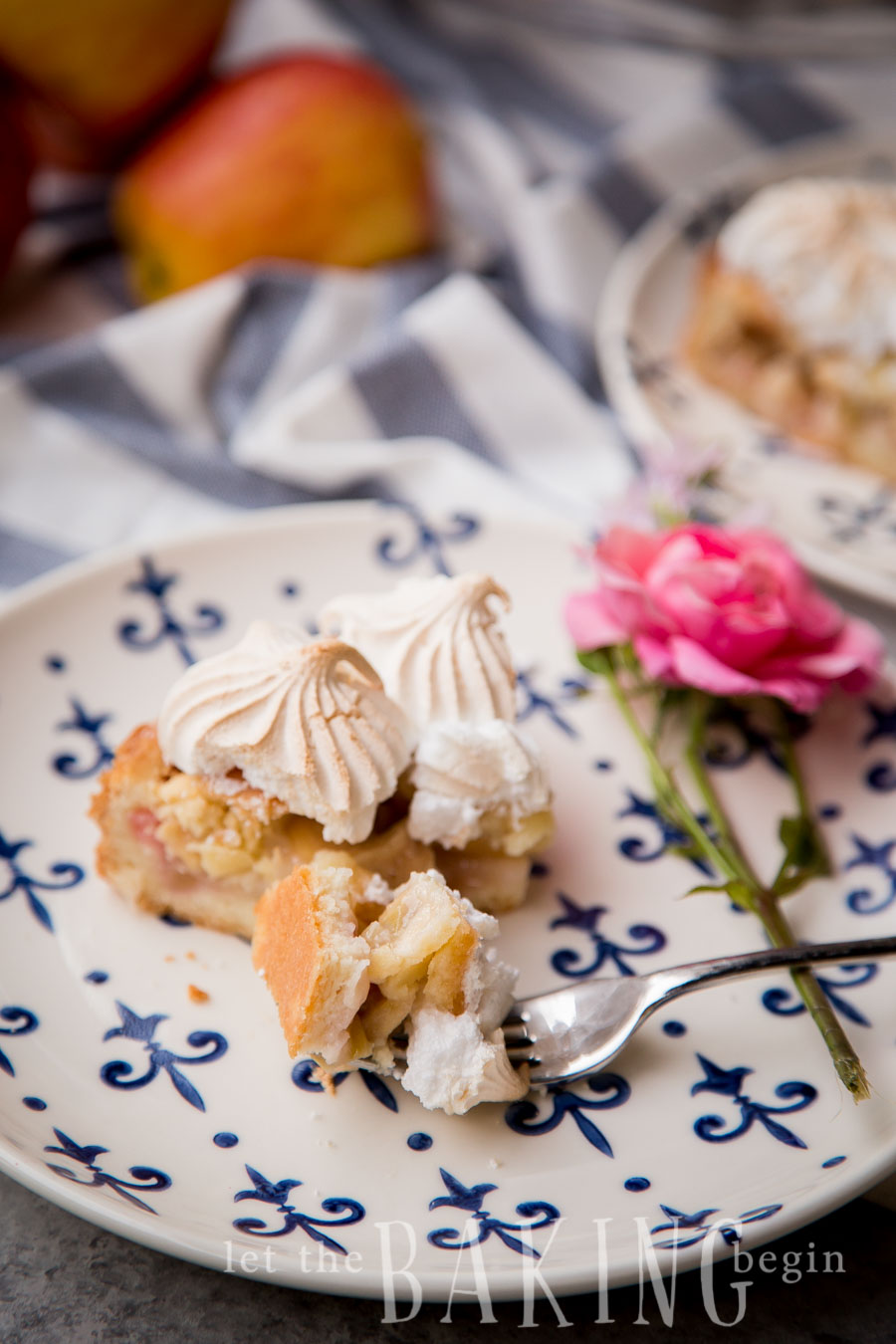 A slice of rhubarb meringue pirog on a white and blue cake with a fork.
