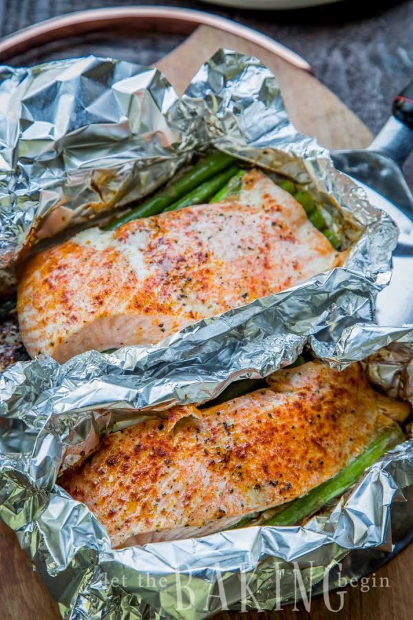 Two salmon asparagus foil packets in a pan.