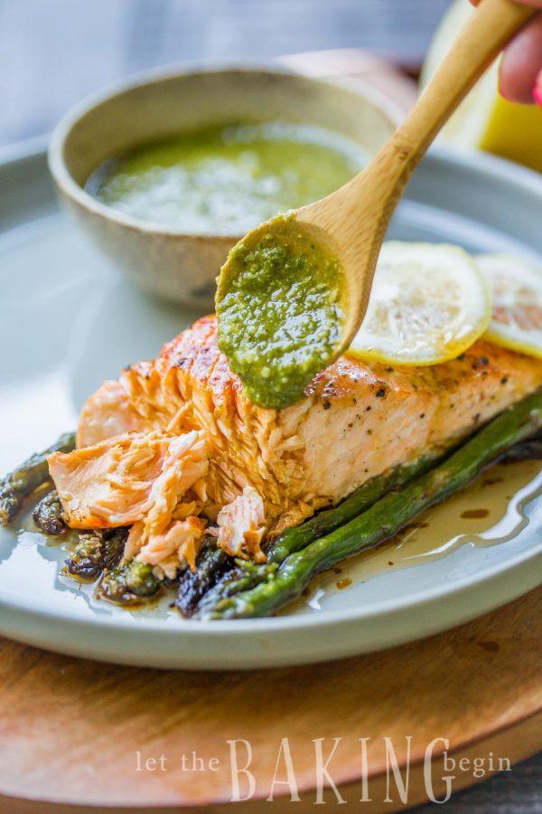 Baked salmon asparagus on a plate with chimichurri sauce.