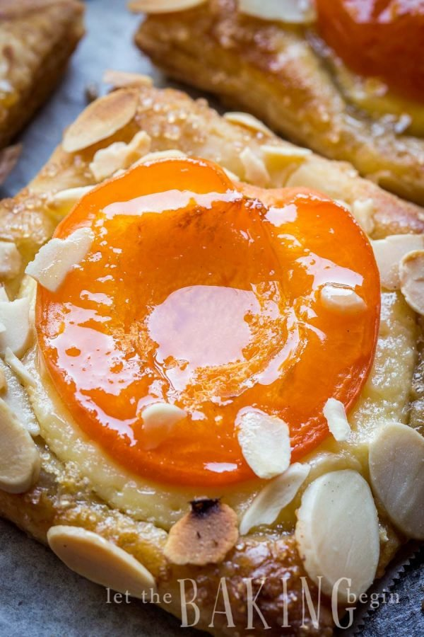 Apricot almond pastry topped with almond slices on a gray napkin.