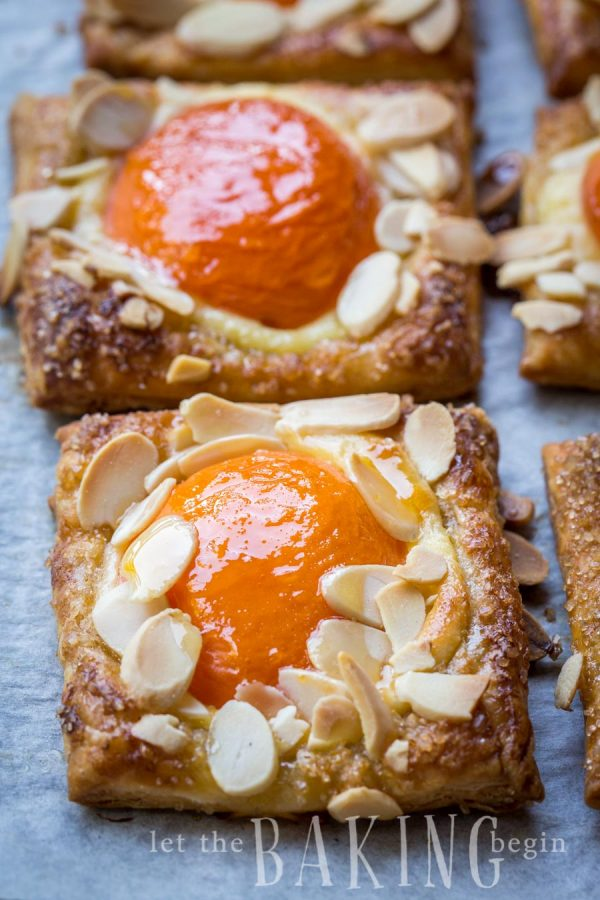 Two apricot almond pastries topped with almond slices on a gray napkin.