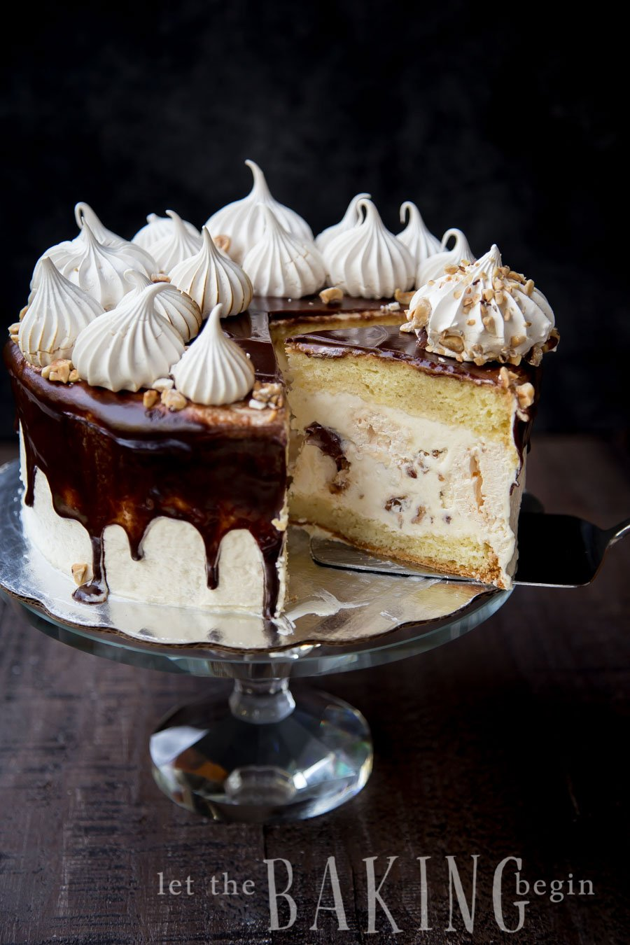 Kiev cake with a slice missing to see inside, topped with chocolate, half meringues, and hazelnuts on a platter.