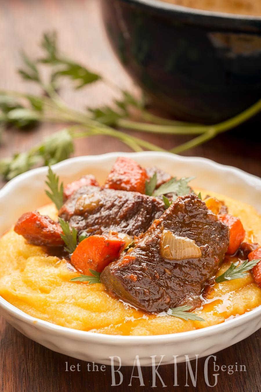 Mashed potatoes topped with vegetables, fresh greens, and braised short ribs in a white decorative bowl.
