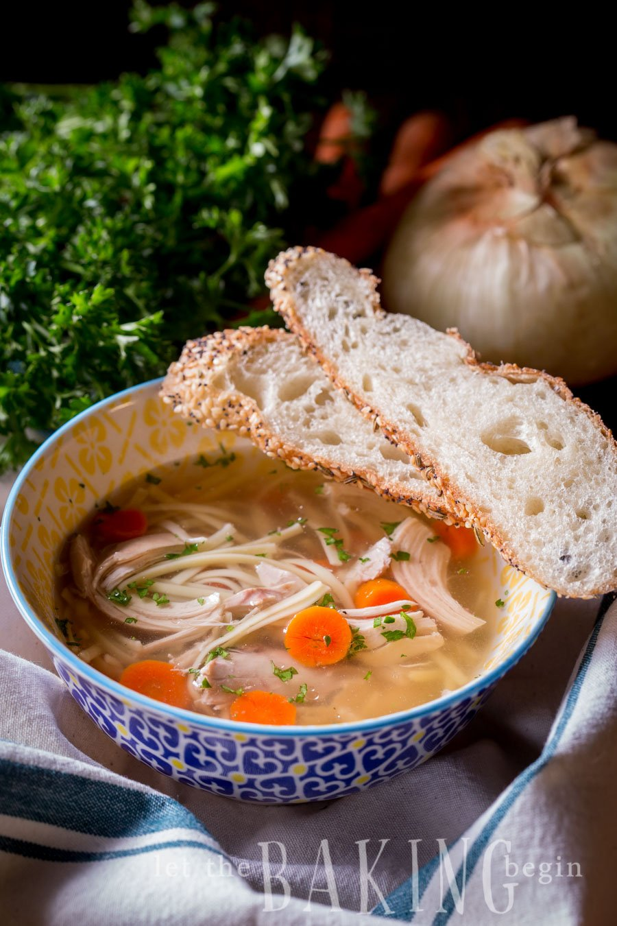 Instant pot chicken noodle soup in a bowl with freshly sliced bread.