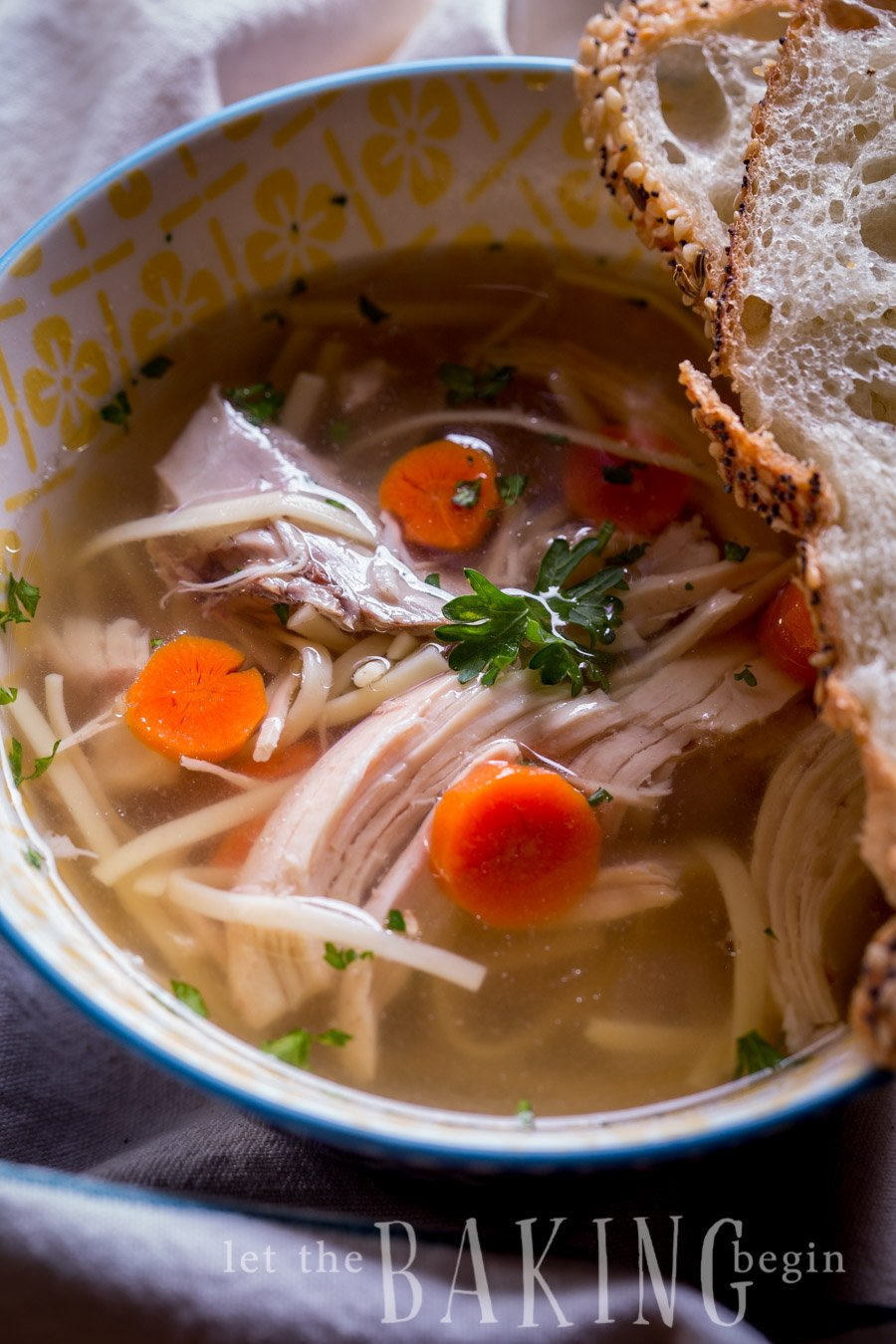 Easy chicken noodle soup recipe in a bowl with sliced bread.