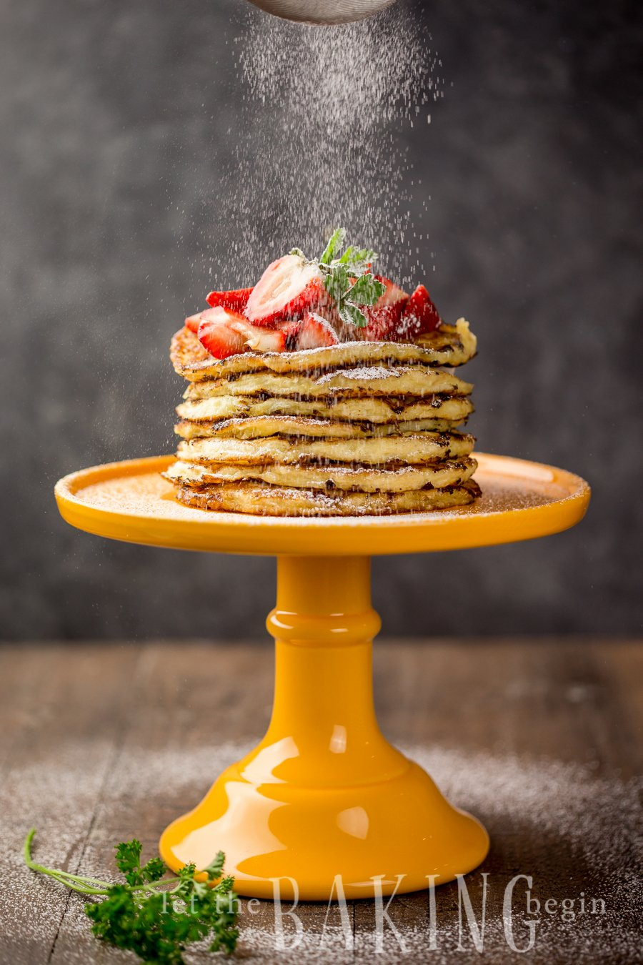 Powdered sugar being sprinkled on a yellow platter of cottage cheese pancakes topped with fresh strawberries.