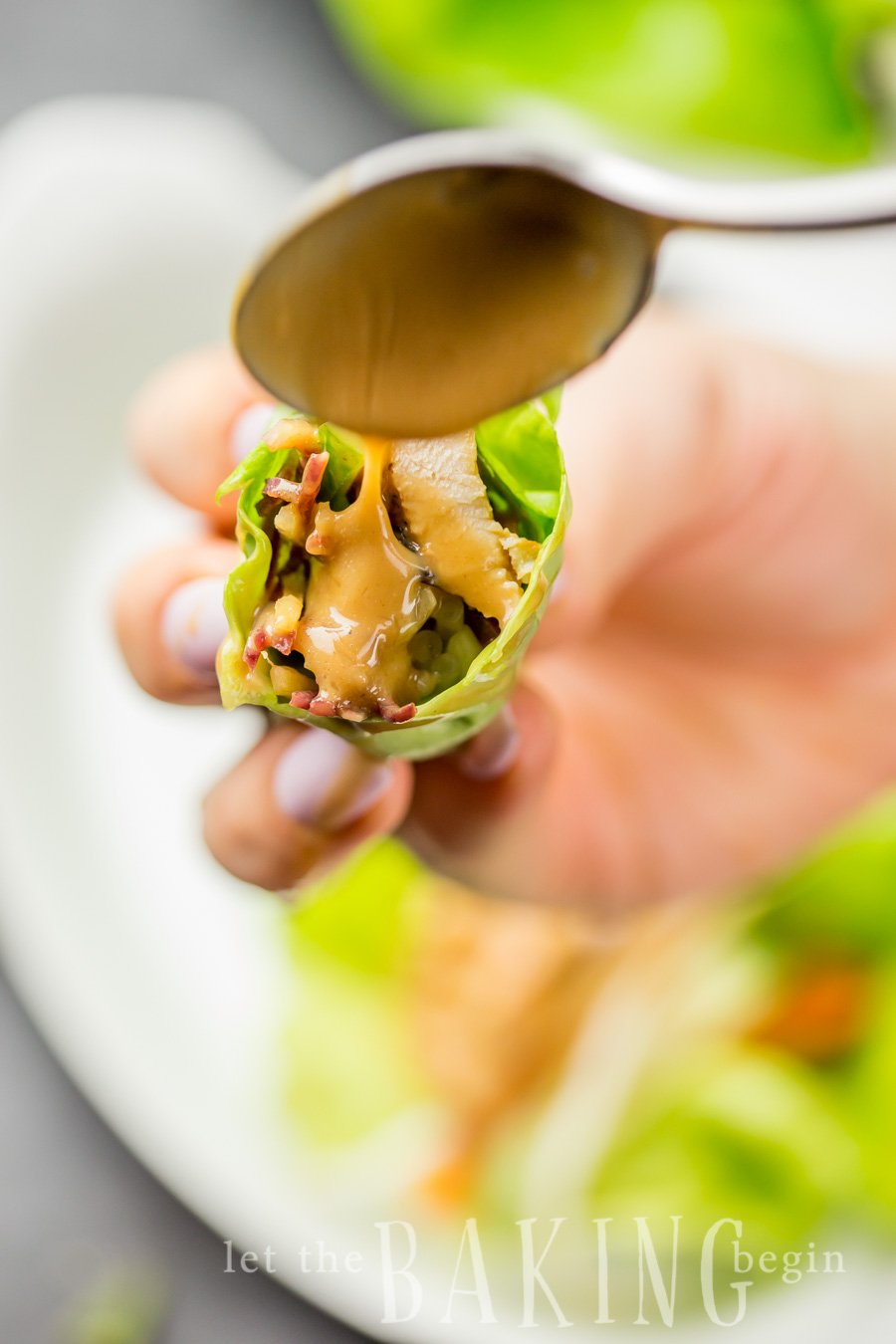 A lettuce wrap with Thai chicken with peanut sauce drizzled on top.