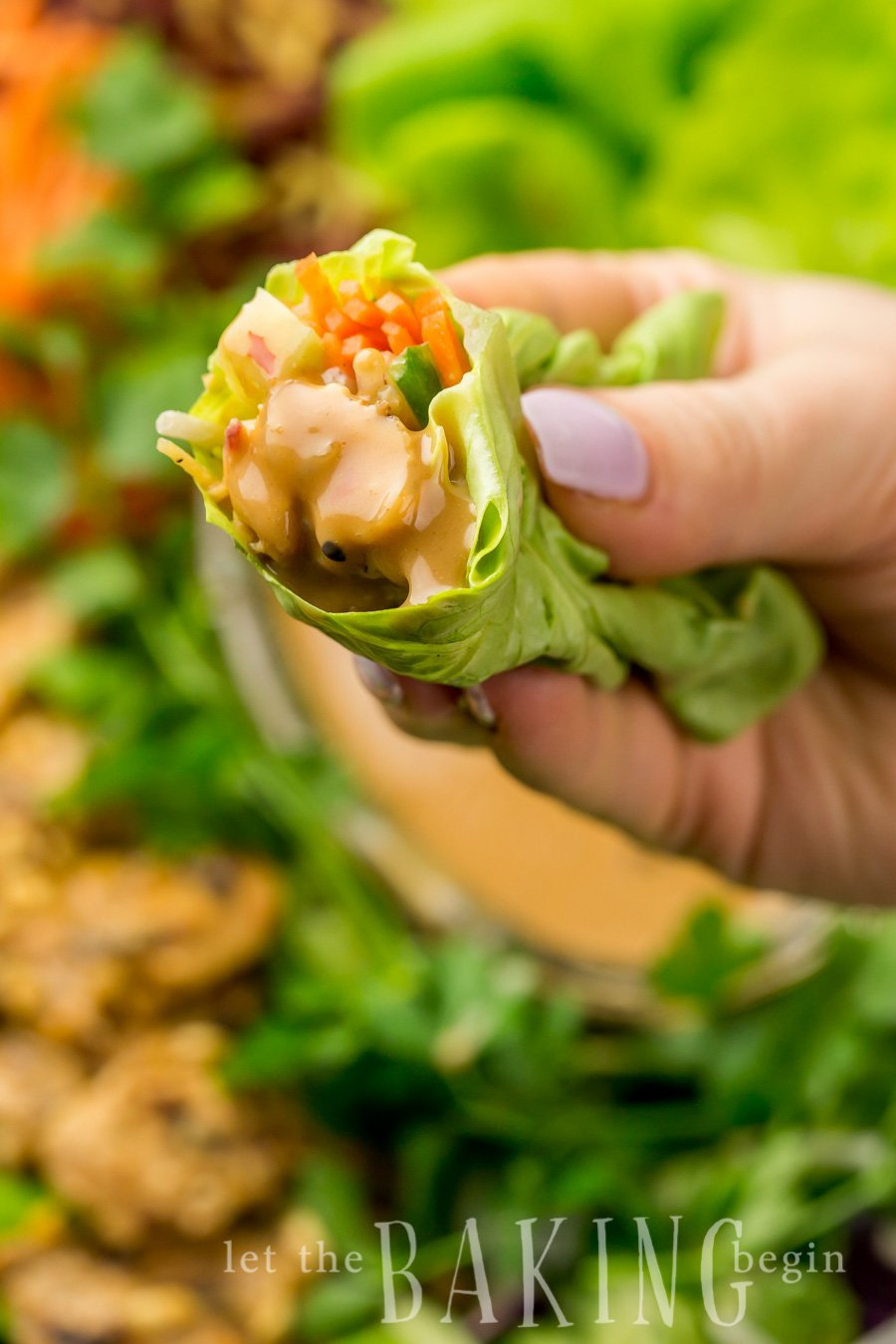 Lettuce wrap with chicken and a peanut sauce wrapped and being held.