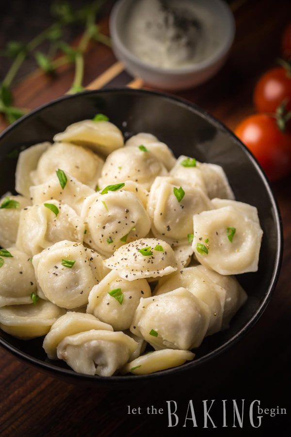 Chicken Pelmeni in a bowl with sour cream on top.
