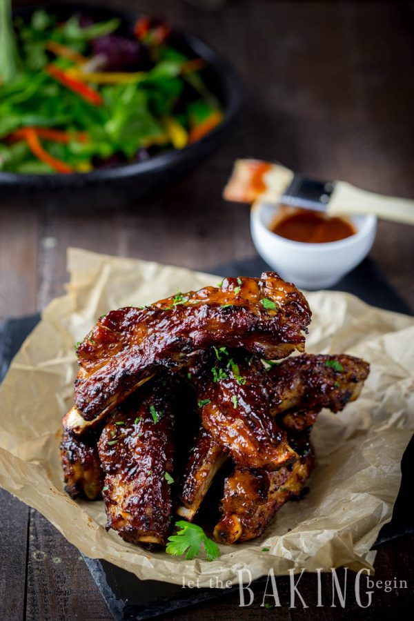 Instant Pot ribs piled with a bbq sauce and a salad in the background.