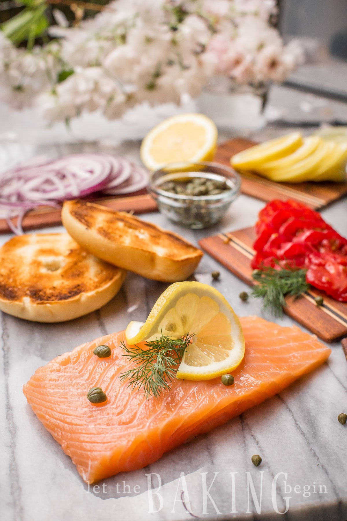 Smoked salmon with fresh lemon and dill, onions and bagel slices.