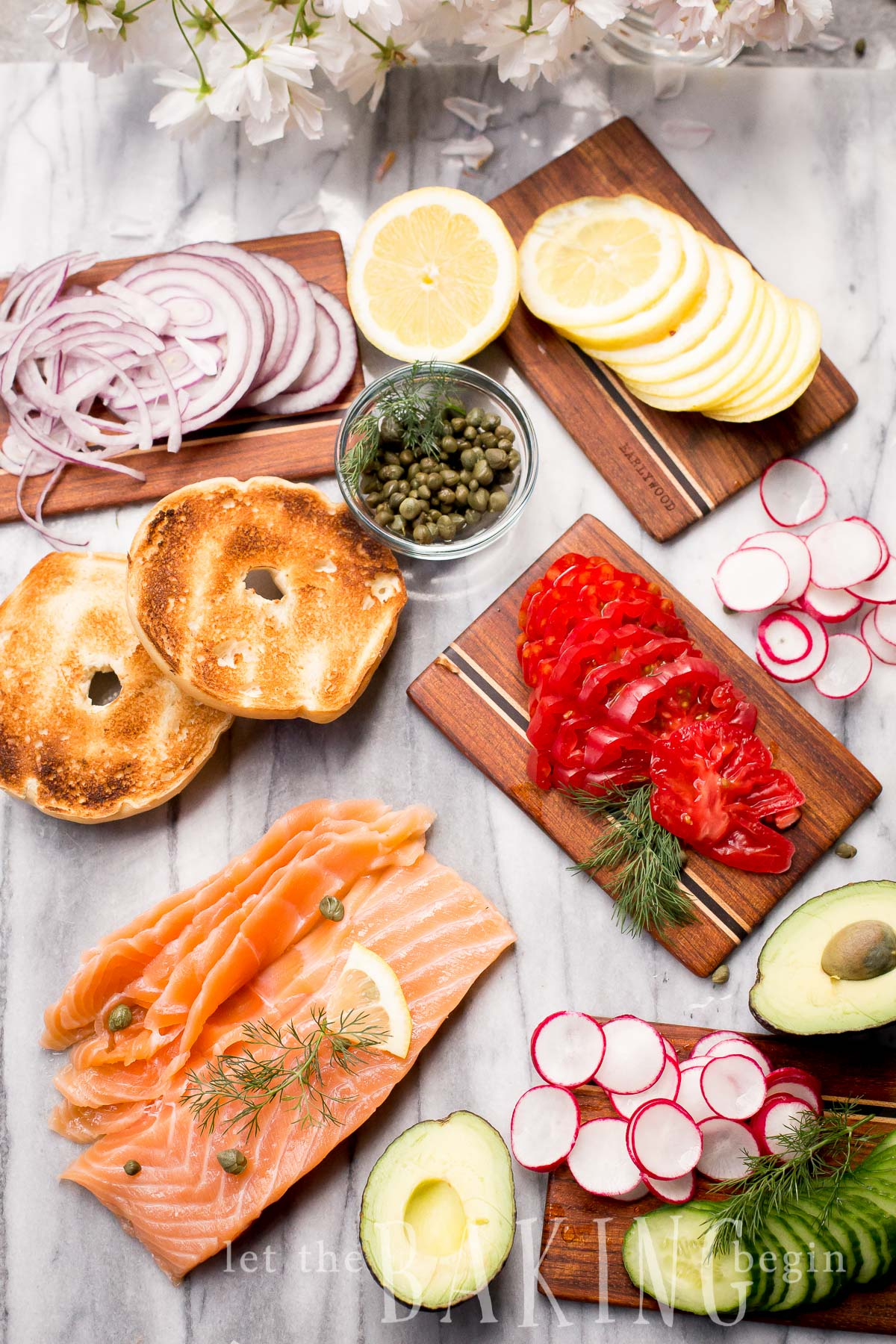 Smoked salmon recipes - this is shown with salmon, bagels, capers, onions, lemons and radish.