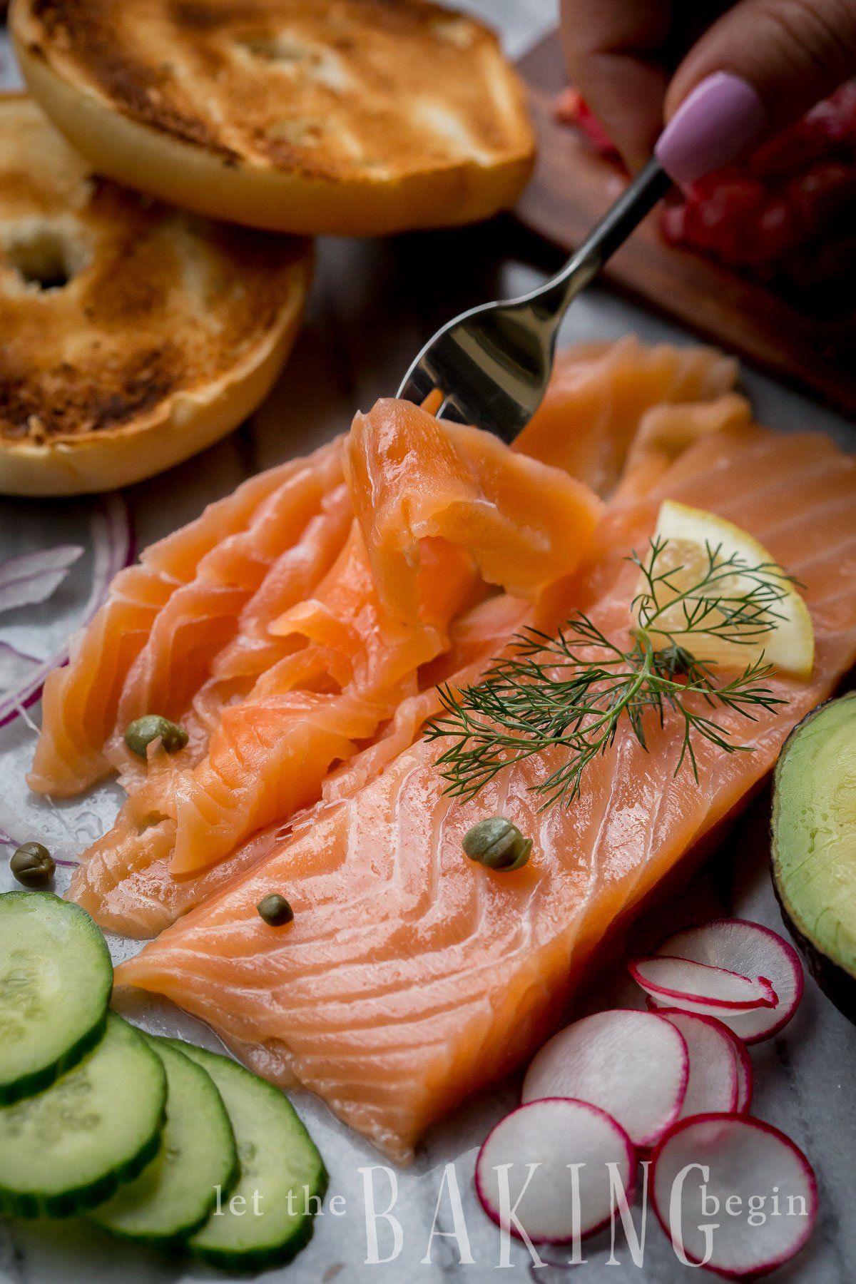 Cold Smoked salmon with capers and fresh dill picked up with a fork.