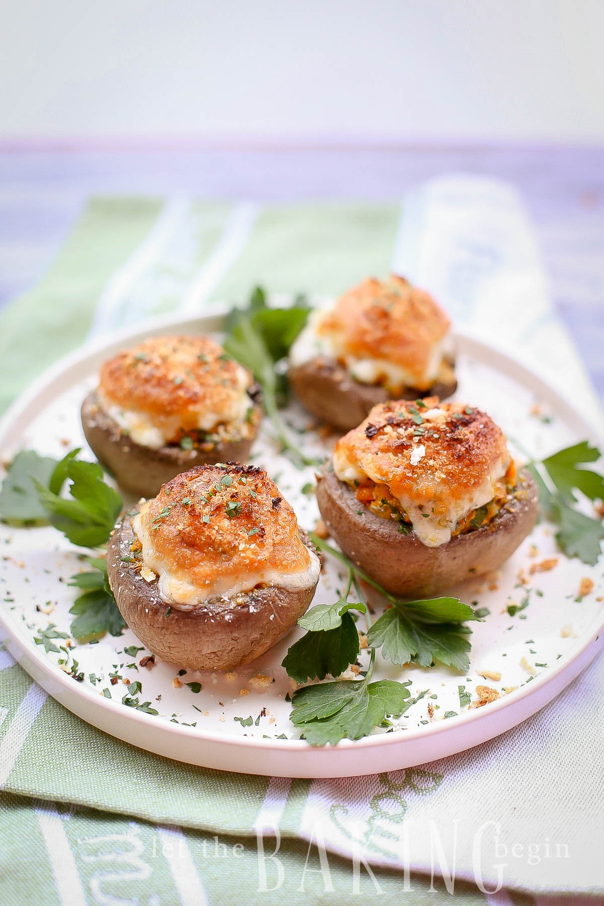 Four cheesy stuffed mushrooms topped with fresh greens on a white tray.
