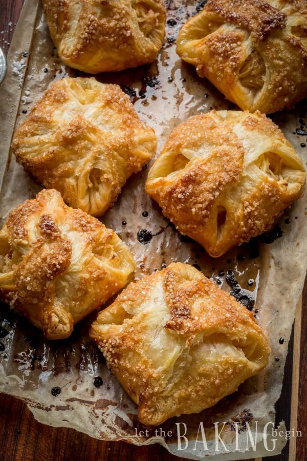Baked apple turnovers with puff pastry lying on baking sheet.