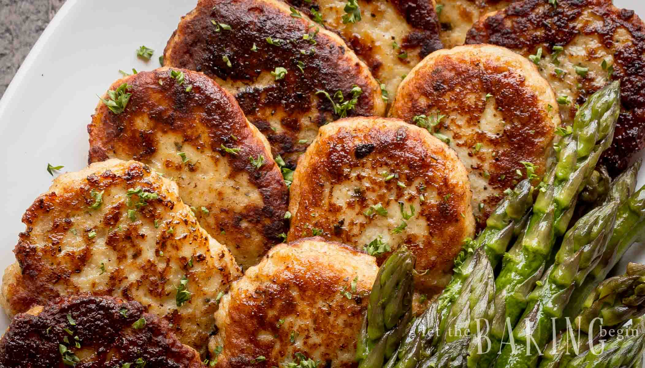 Close up of the best chicken thigh recipe - kotleti. Freshly seasoned patties with fresh herbs and a side of asparagus.