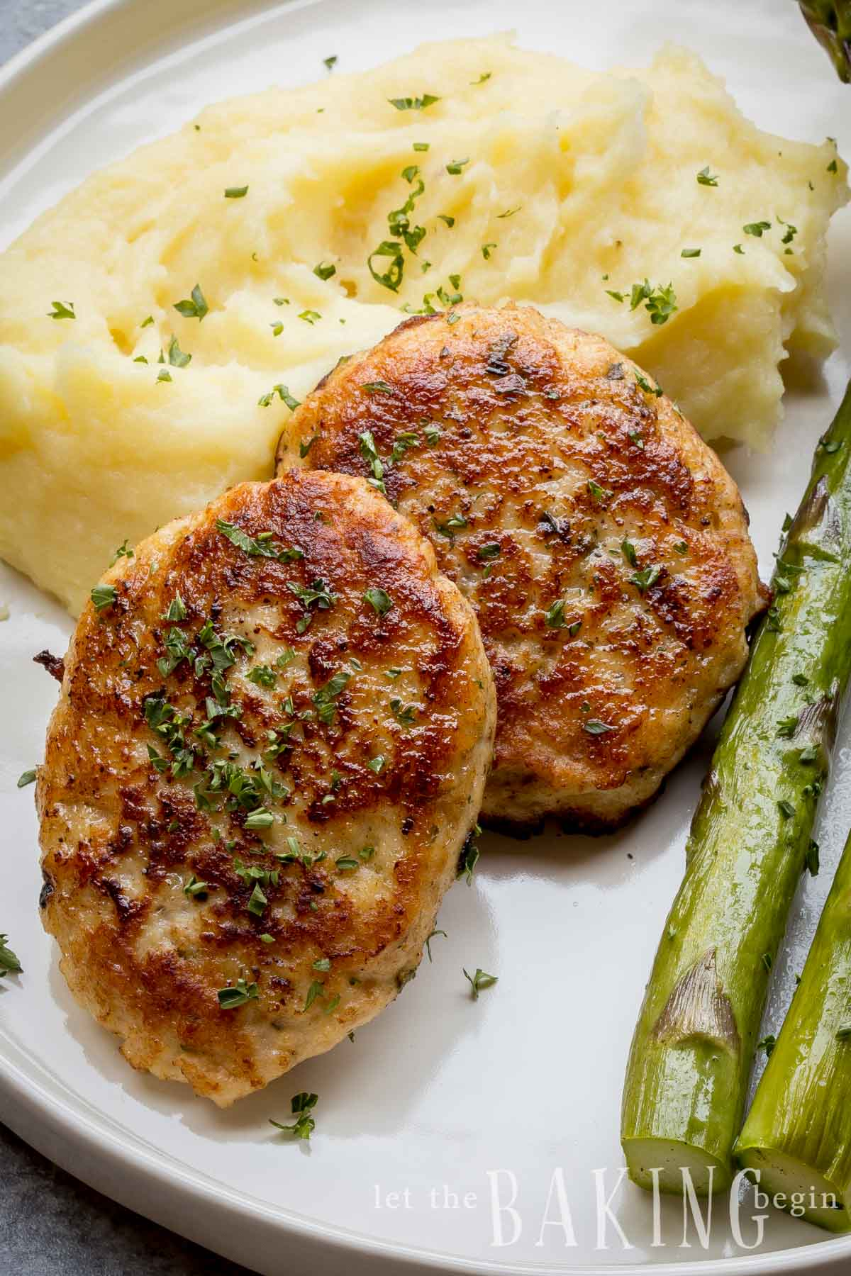 Homemade chicken sausage on a plate with mashed potatoes and asparagus.
