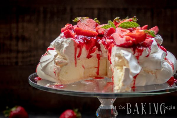 Strawberry Pavlova on a cake stand with one slice gone.