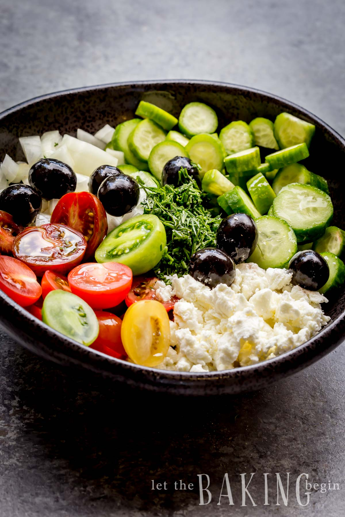 Cucumber tomato salad in a bowl piled with fresh herbs, veggies and cheese.