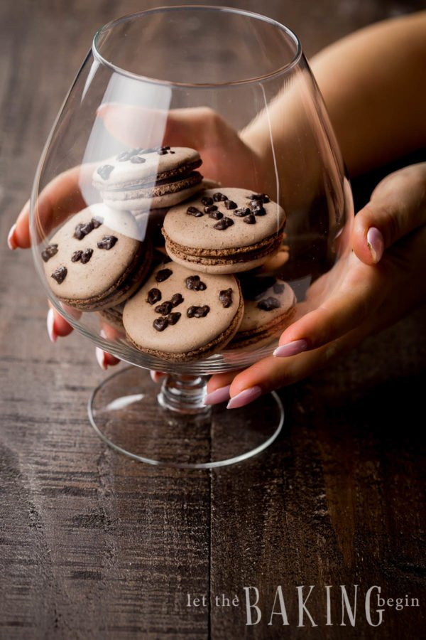 Woman holding a large footed glass dish filled with hazelnut macarons