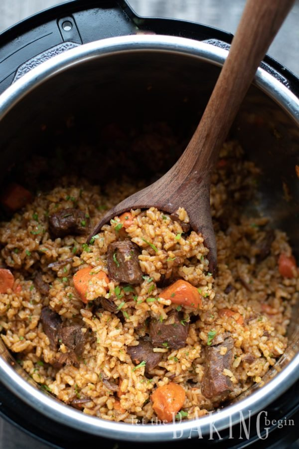 Beef rice pilaf (plov) with a wooden spoon in an instant pot.