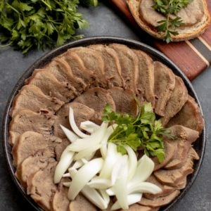 Sliced Beef Tongue on a plate with Onion and Herbs.