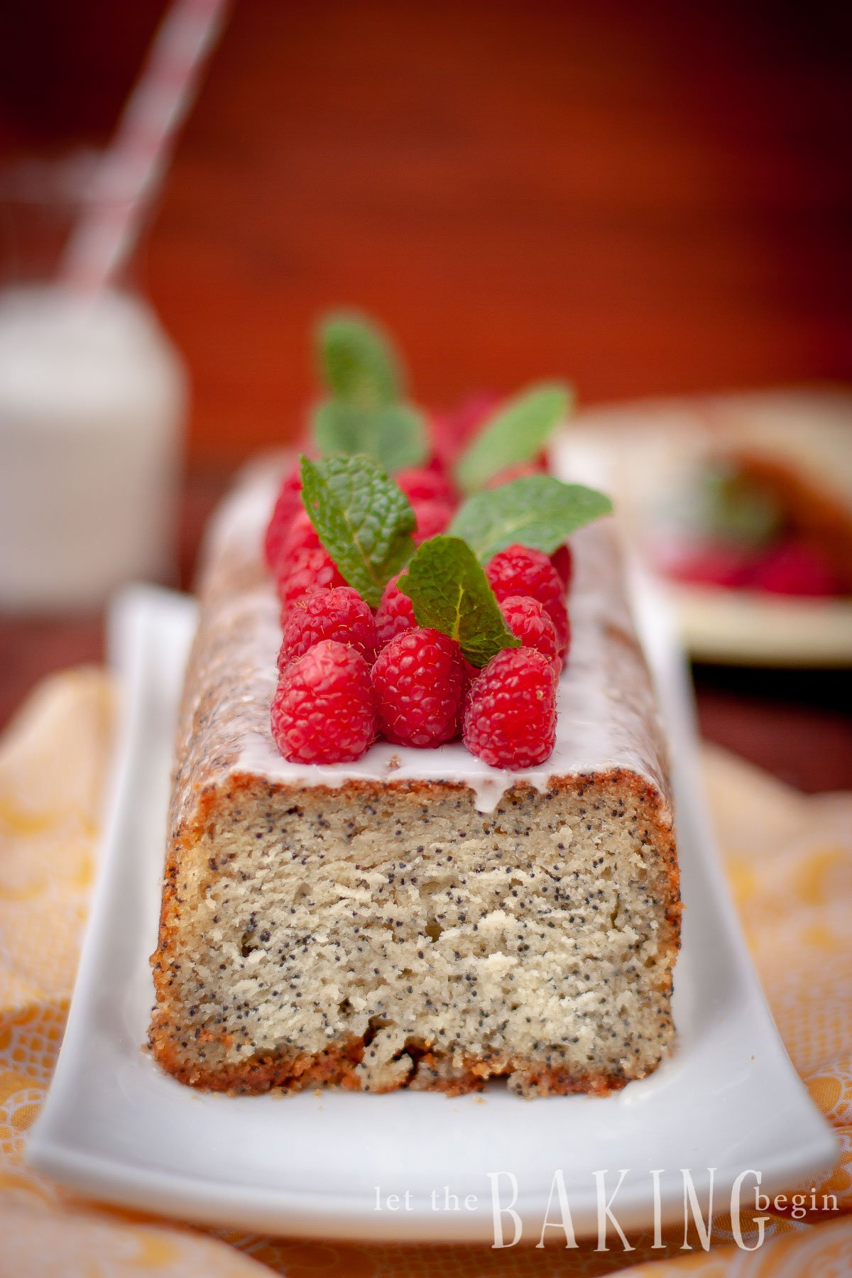 Lemon Poppy seed Cake on a platter topped with fresh raspberries and mint leaves.