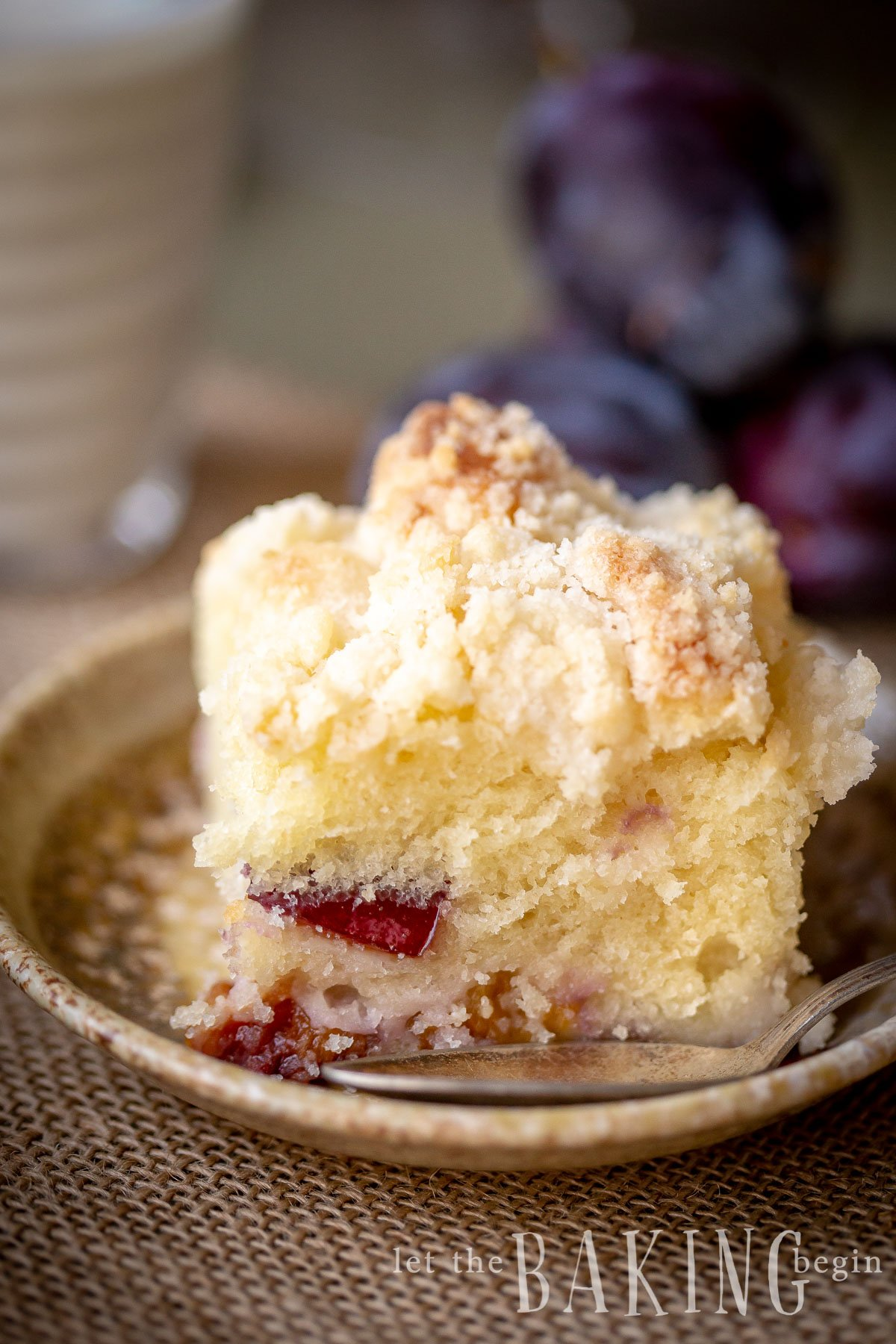 Soft pillow Plum Coffee Cake on a decorative plate topped with a streusel topping.