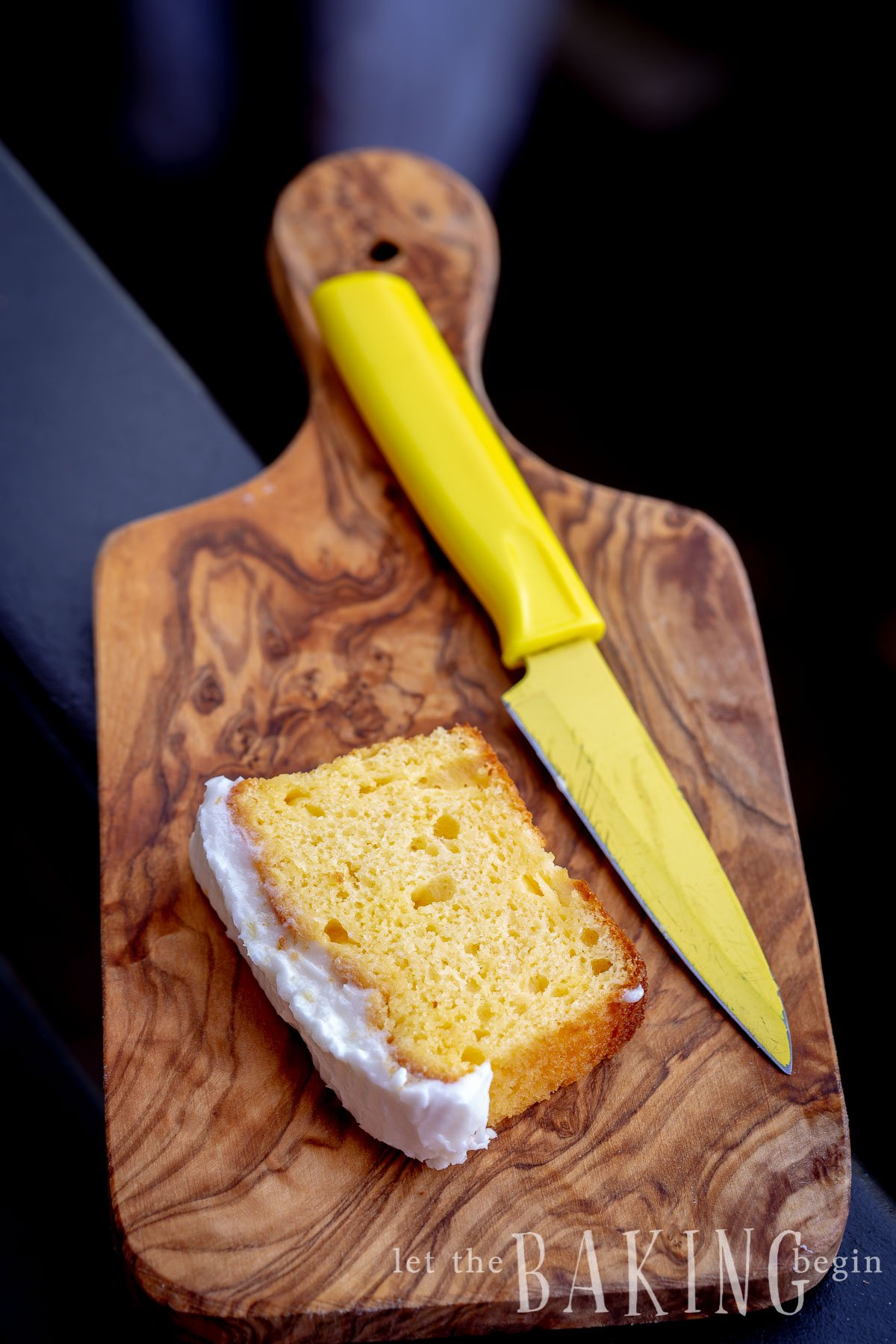 A slice of lemon loaf cake on a cutting board with a knife.