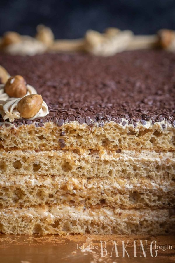 Four layer cake with chocolate shavings and roasted hazelnuts made from a caramel cake recipe.