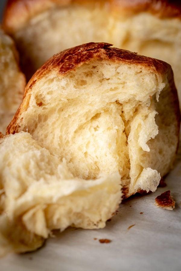 Brioche Roll is torn open, exposing beautiful strands of rich brioche dough.