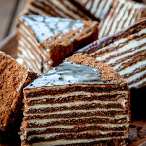 Chocolate layer cake with sour cream frosting on a plate surrounded by cake slices