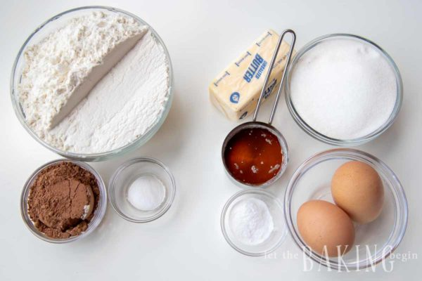 Ingredients needed for Spartak cake such as flour, cocoa, eggs, and butter