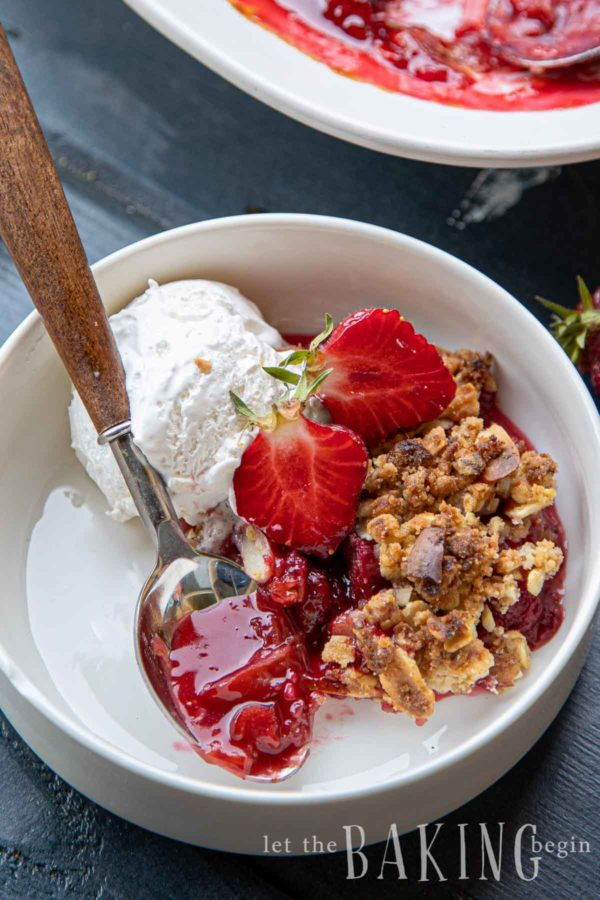 Strawberry rhubarb crisp recipe in a bowl with a scoop of ice cream and spoon