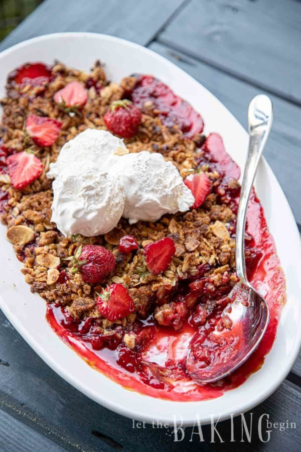 Strawberry rhubarb crisp recipe in a white porcelain baking dish topped with strawberries and ice cream